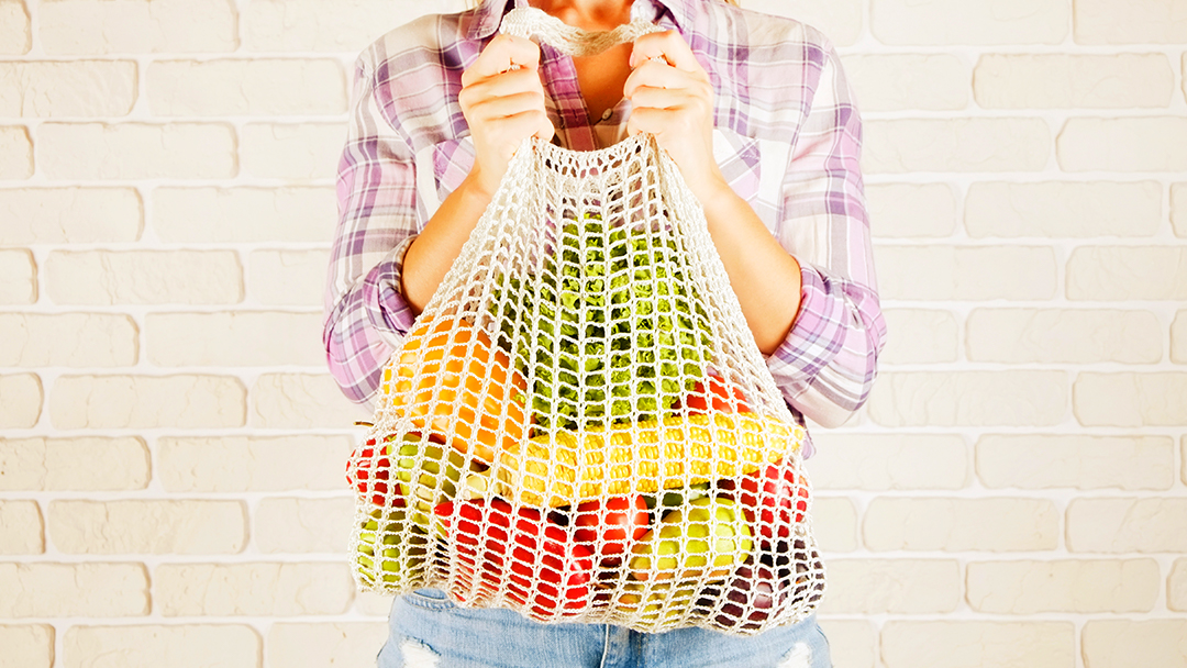 Woman holding recycled bag full of fruits and vegetables