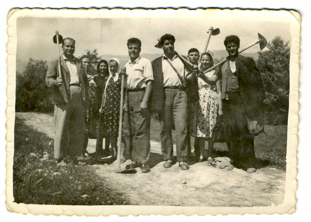 Historical photo of farm villagers with their tools
